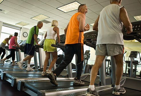 A group of people walk on treadmills.