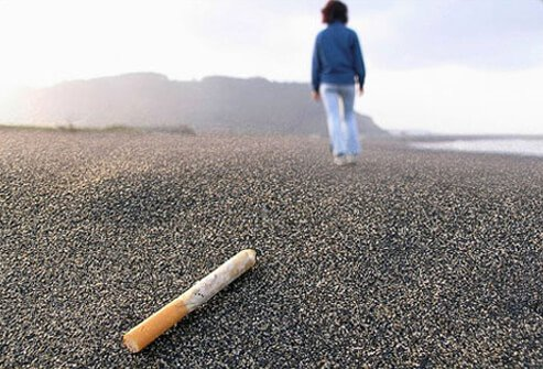 Woman walking away from a cigarette.