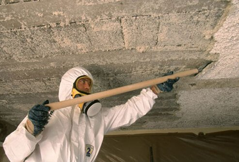 A worker scraping asbestos from a ceiling, exposing himself to harmful chemicals.