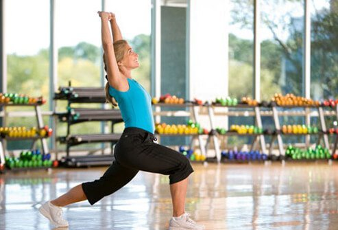 A woman stretching in a fitness studio, staying healthy through menopause.