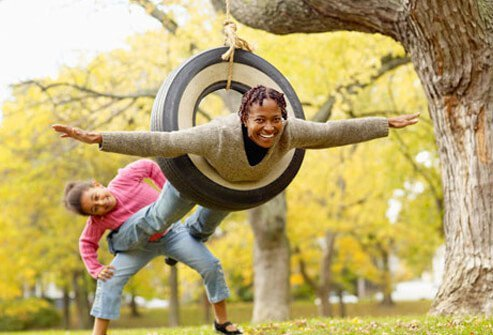 A grandmother and granddaughter playing on a swing, celebrating menopause.