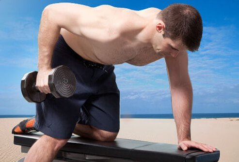 The dumbbell row works your lats as well as the rhomboid muscles in your upper back.