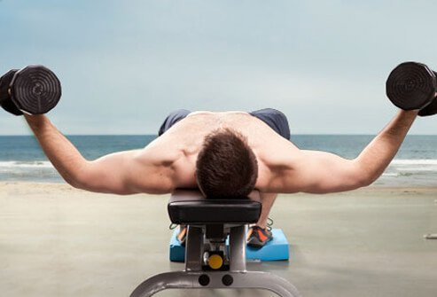 Lie on your back with a dumbbell in each hand.