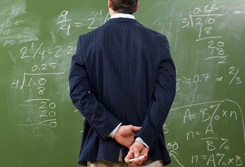 A man solving a math problem on a chalkboard.