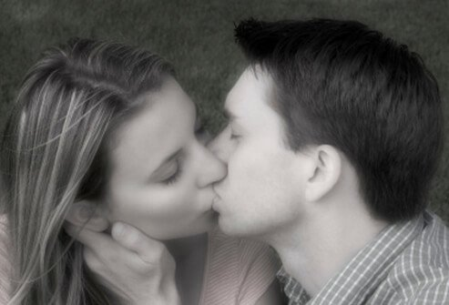 A young couple kisses.