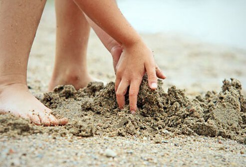A child plays in the sand.