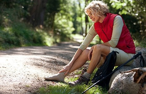 A woman hiker on sitting on the side of the path massaging her leg and foot.