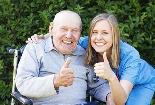 A senior patient and nurse giving a thumbs up.