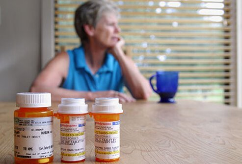 A senior woman with prescription medication bottles.