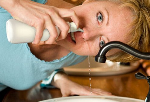 A woman doing a nasal rinse.