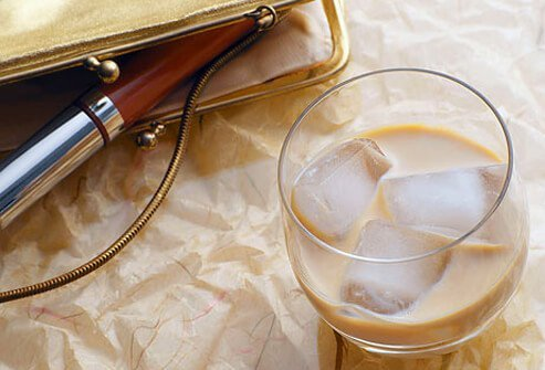 Mixed drink next to an evening bag with lipgloss.