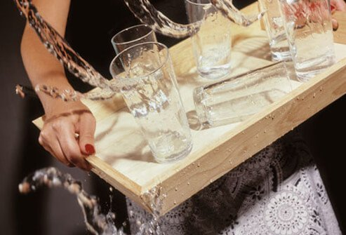 A woman spilling a tray of water glasses.
