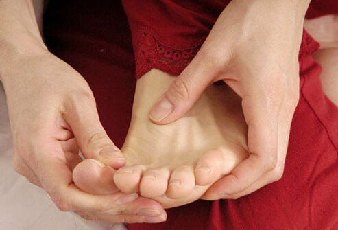A woman touching her foot.