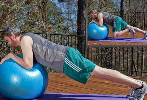 Photo of a man performing the dynamic plank with exercise ball.