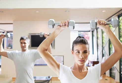 Photo of a couple exercising in their home gym.