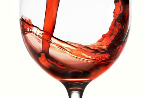 Red wine being poured into glass, close-up.