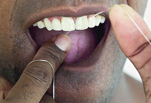 Man cleaning his teeth with dental floss.