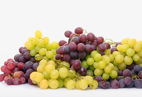 Red and green grapes on a white background.