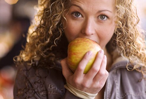 A young woman biting into an apple.