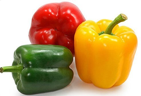 Green, red, and yellow bell peppers on a white background.