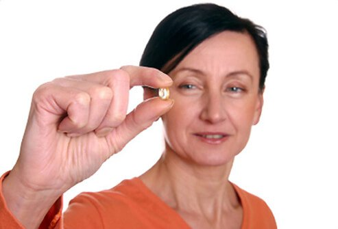 A woman takes her hormone replacement therapy pill.