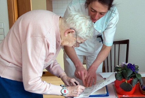 A senior woman with osteoporosis signs documents for a nurse.