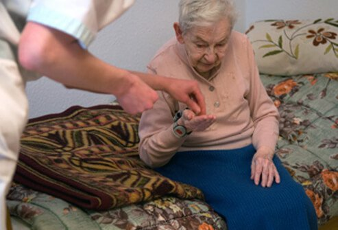 A nurse helps a senior woman with osteoporosis stand up.