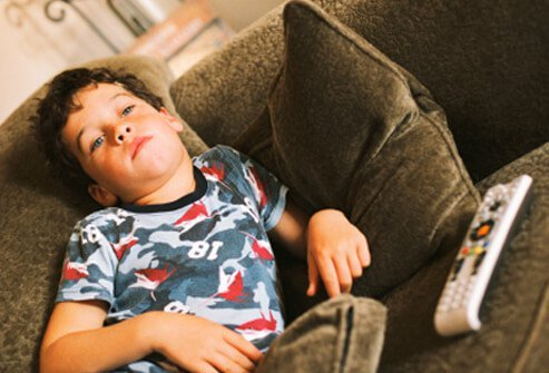 A young boy lazes on the couch while watching TV.