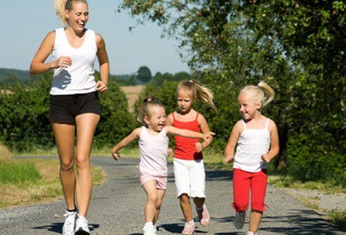 A mom jogs with her daughters.
