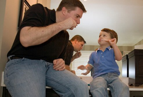 A father shows his son how to brush his teeth.