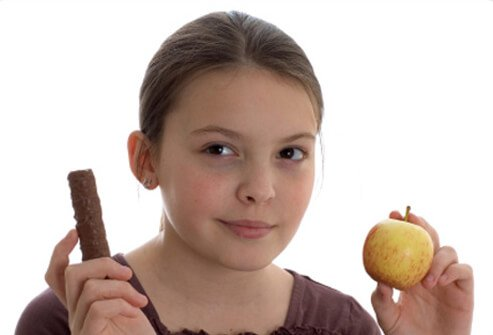 A young girl is tries to decide whether to eat a chocolate bar or an apple.