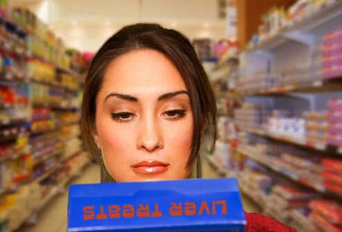 Photo of woman reading pet food ingredients.