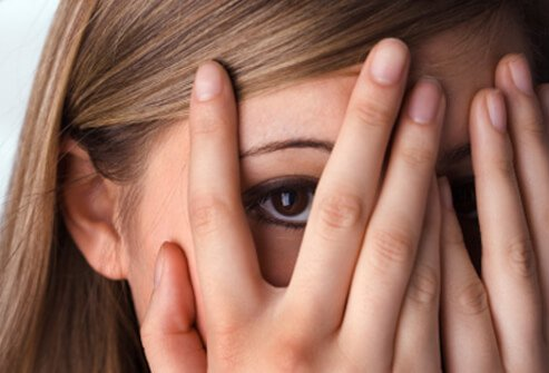 A woman covers her eyes from some type of phobia.