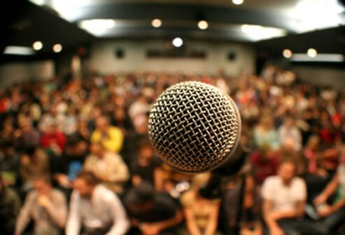 A microphone looms large in front of a huge group of people.