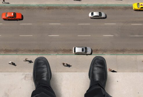 A man on the ledge of a high-rise building looks down to the street below.