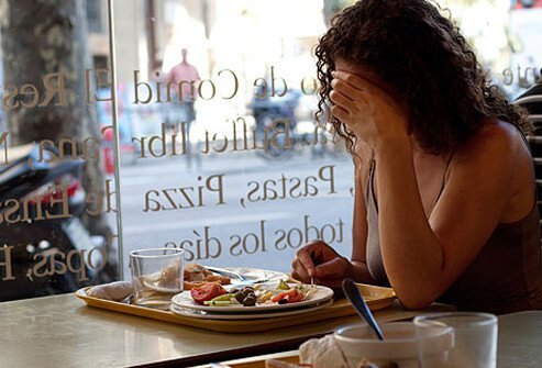Photo of a depressed woman with a lack of appetite.