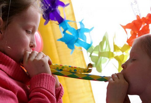 Two girls blow noisemakers at a party.