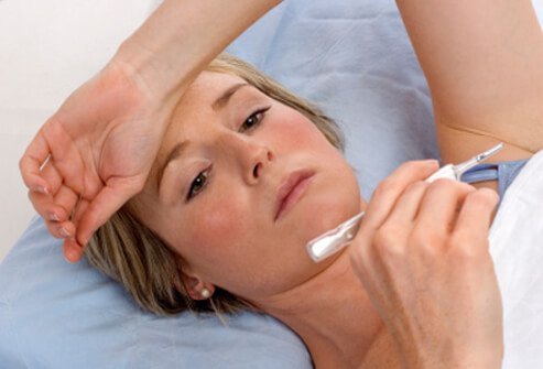 A woman checking her basal body temperature upon waking.