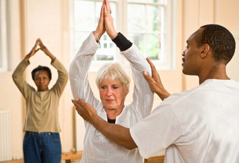 Personal trainer helping woman in exercise class.
