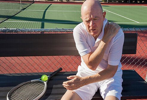A senior tennis player grips an aching shoulder.