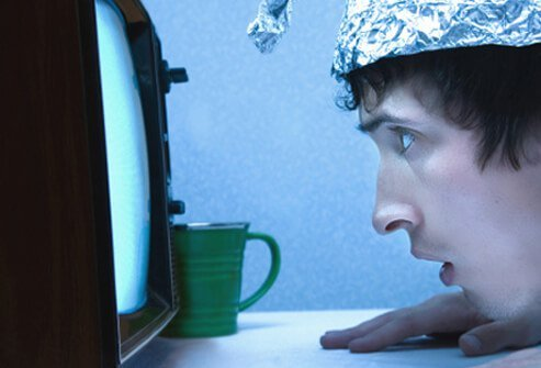 A young man with undifferentiated schizophrenia wears a tinfoil hat while staring into a TV.
