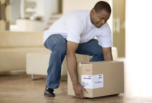 Photo of a man lifting a box from the floor.