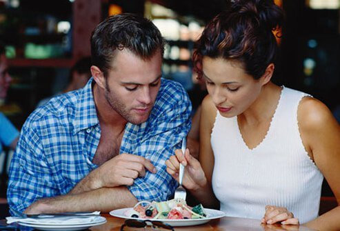Photo of couple sharing salad.