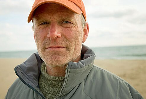 Man with sun damage wearing baseball cap on beach.