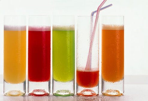 Five colorful glasses of juices with one that is almost finished.
