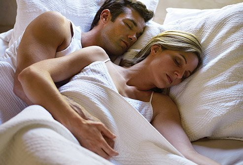 Spooning is a side sleeping position for couples. The person in the back holds the one in the front close to their body.