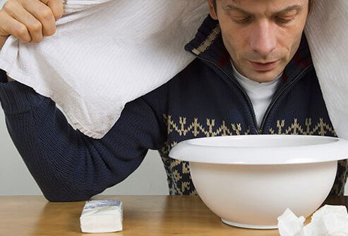 Man with a cold breathing steam from a bowl.