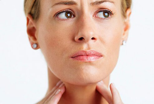Woman feeling her neck due to a sore throat.