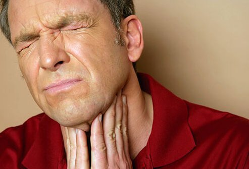 Man holding his throat in extreme discomfort due to a sore throat.