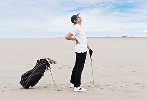 A man suffering low back pain while golfing.